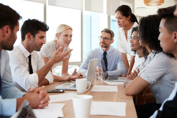 Group Of Businesspeople Meeting Around Table In Office - Photo