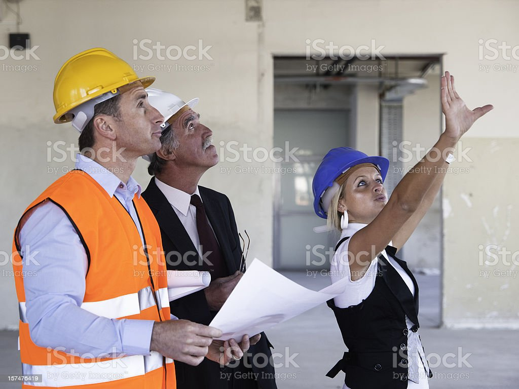 Group of Businesspeople Reviewing Blueprints Together on Construction Site royalty-free stock photo