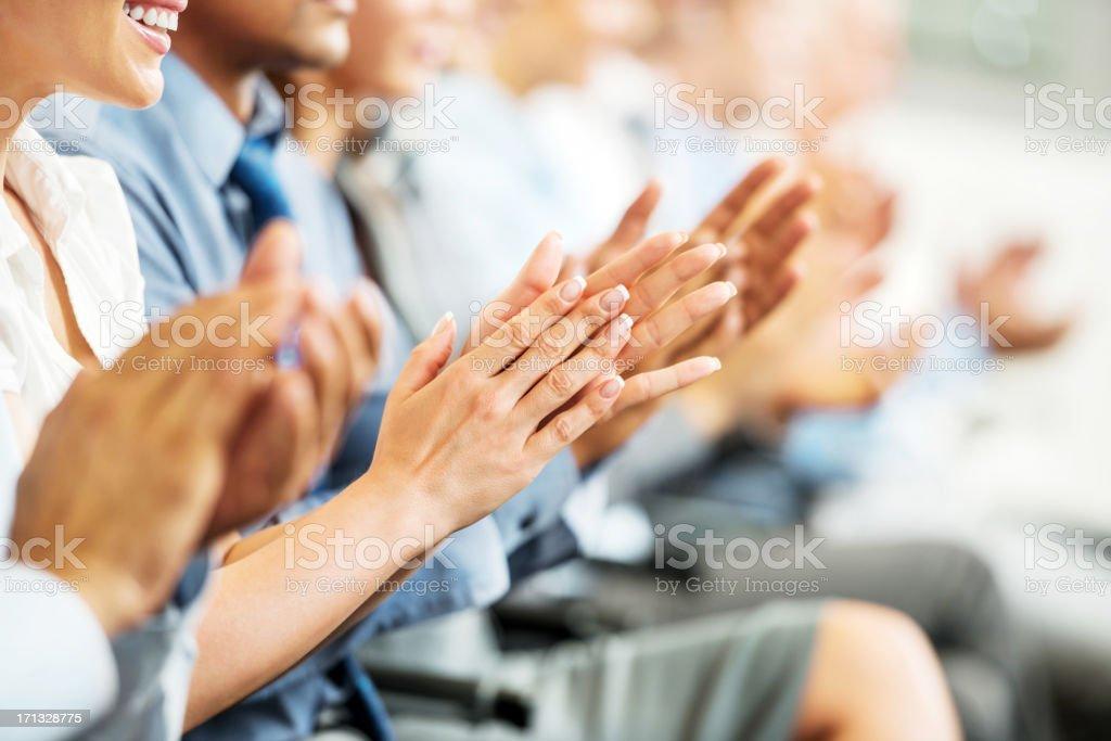 Grupo de empresários sentado em uma linha e a aplaudir. - foto de acervo