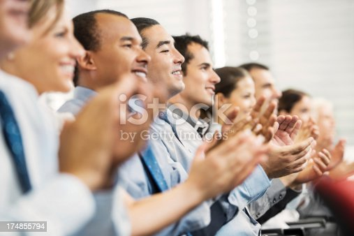 640177838 istock photo Group of businesspeople sitting in a line and applauding. 174855794