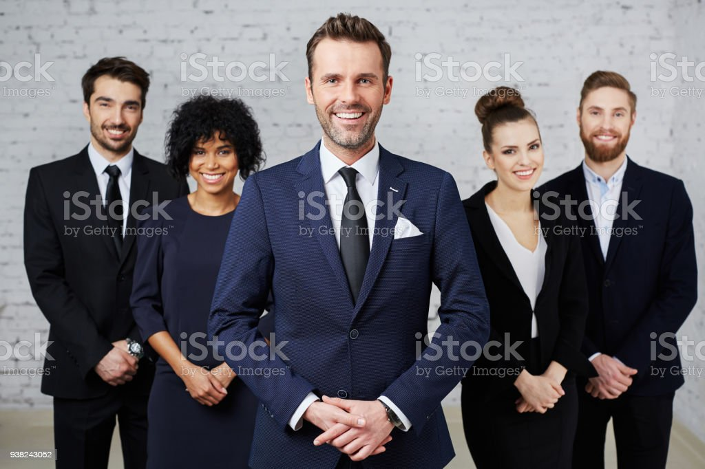 Group of businesspeople standing as a team with happy teamleader at front stock photo