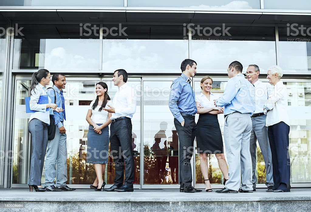 Group of businesspeople standing in front office building royalty-free stock photo