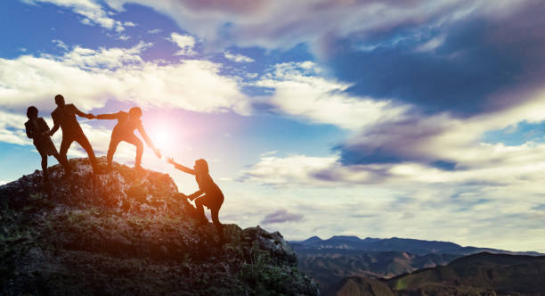 Group of businessperson climbing a mountain. Challenge of business concept. stock photo
