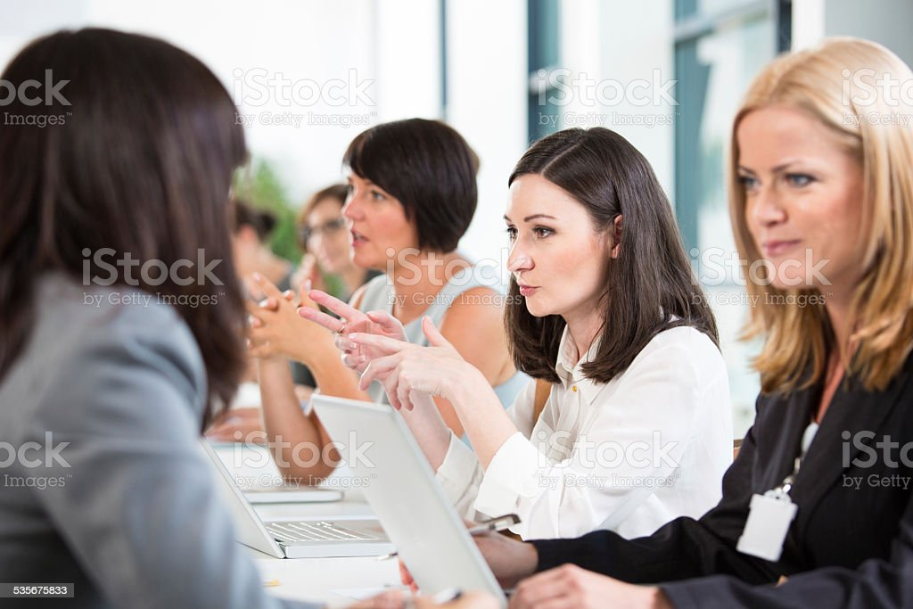 Group of businesswomen at meeting Group of businesswomen brainstorming, working together and discussing in an office. 2015 Stock Photo