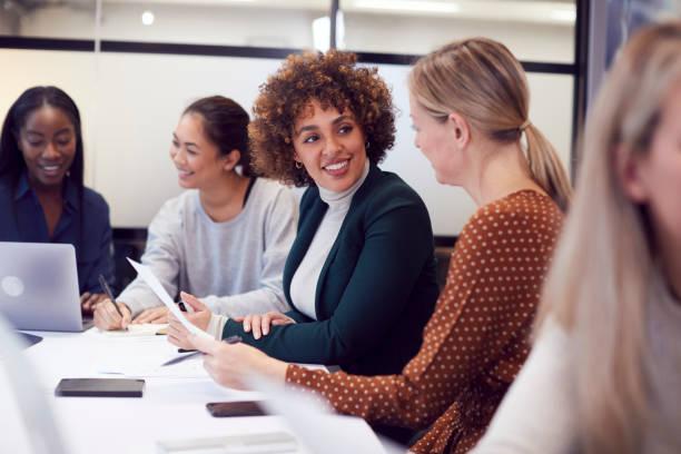 在現代辦公室,女企業家們合作在餐桌上舉行創意會議。 - 女人 個照片及圖片檔