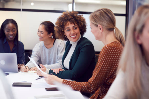 Group Of Businesswomen Collaborating In Creative Meeting Around Table In Modern Office stock photo