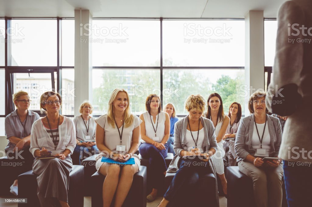 Group of businesswomen during seminar Group of business women listening to the speaker during training. Women attending a seminar. Adult Stock Photo
