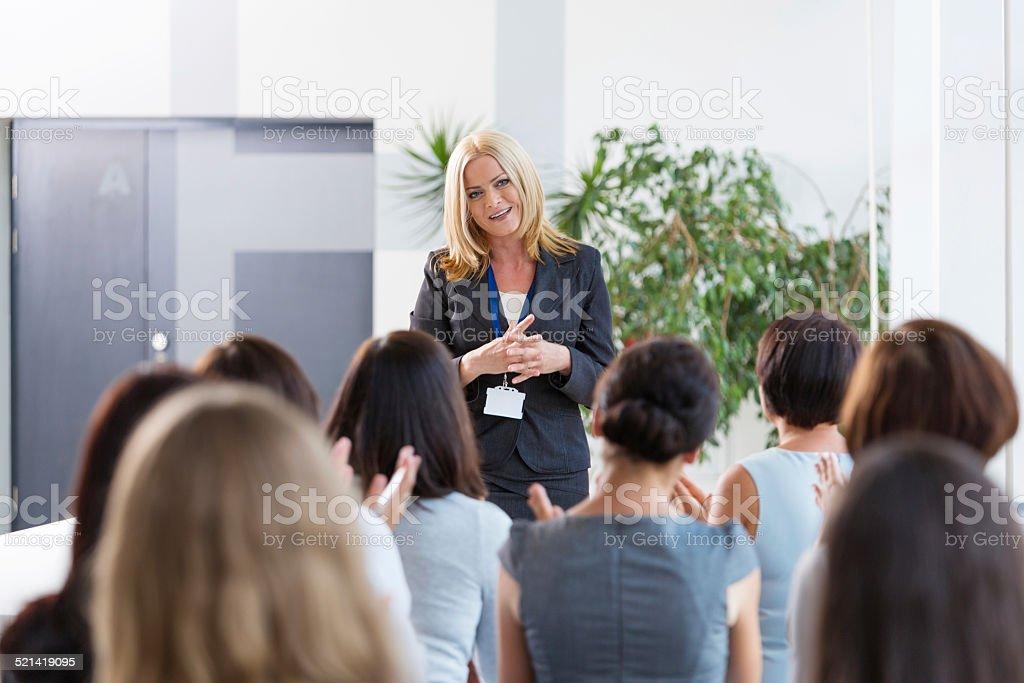 Group of businesswomen during seminar Back view of group of businesswomen attending a seminar. Focus on the female coach having speach. Achievement Stock Photo