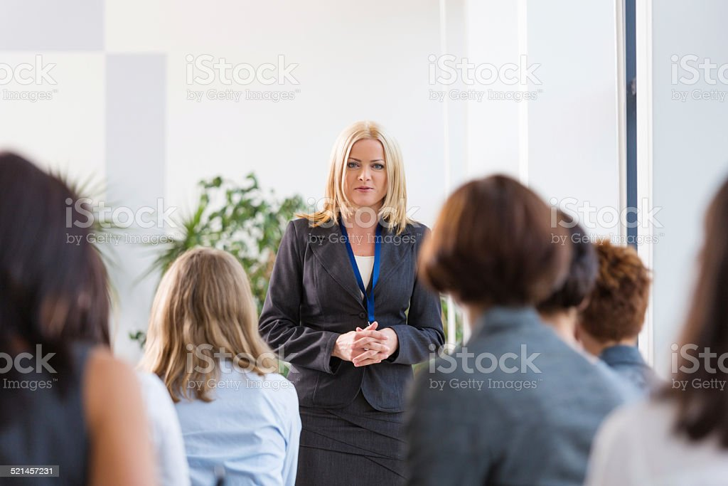 Group of businesswomen during seminar Back view of group of businesswomen attending a seminar. Focus on the female coach. Achievement Stock Photo