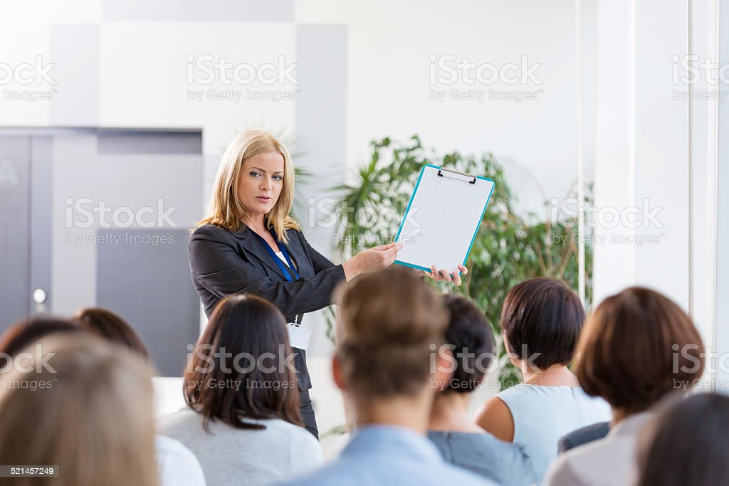 Group of businesswomen during seminar Back view of group of businesswomen attending a seminar. Focus on the female coach pointing at clipboard. Achievement Stock Photo