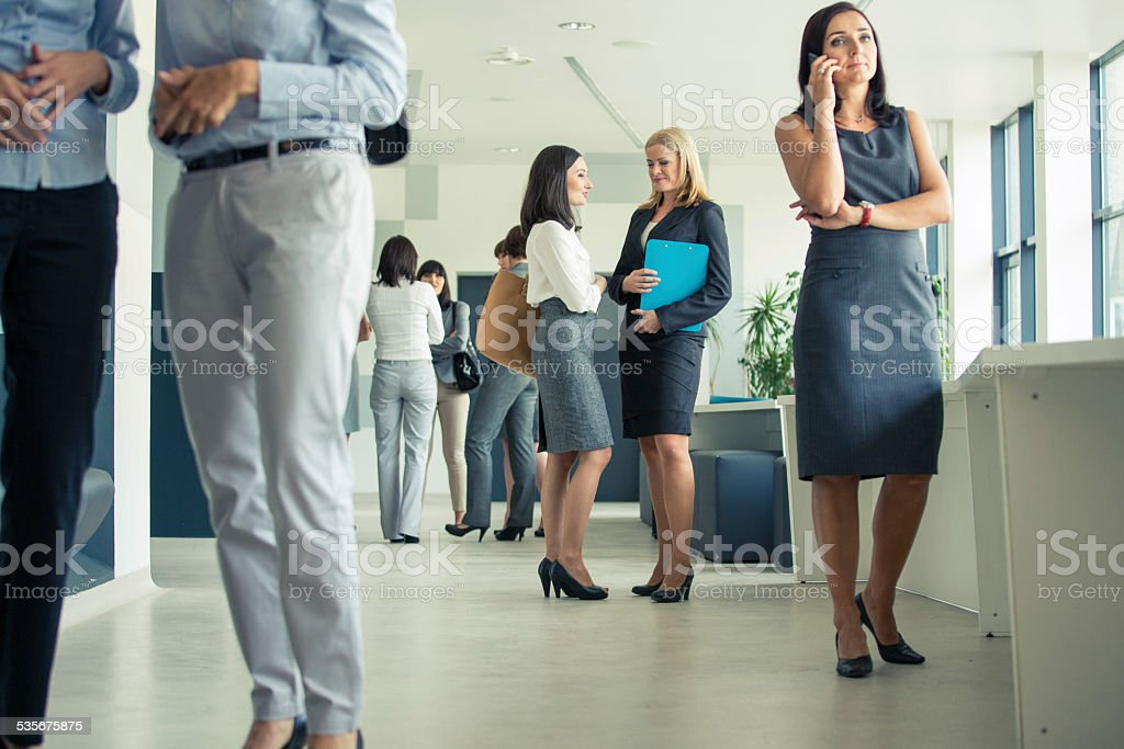 Group of businesswomen in an office corridor Group of businesswomen having break during conference, standing in the hall in modern office. Woman on the right site talking on phone. 2015 Stock Photo