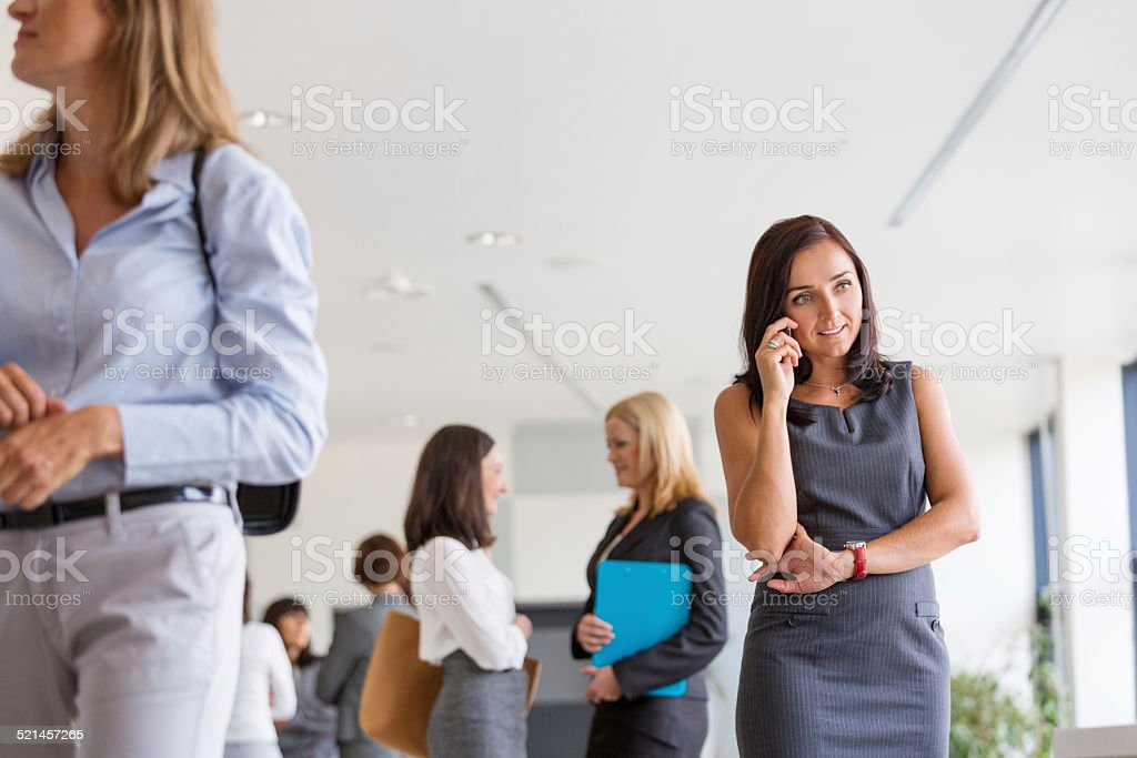 Group of businesswomen in the office Group of businesswomen standing in the hall of modern interior and having chat. Focus on the woman talking on phone. Adult Stock Photo