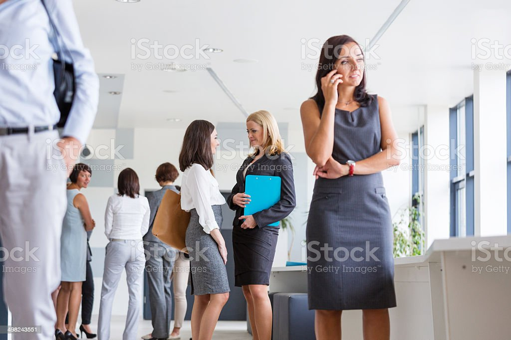 Group of businesswomen Group of businesswomen standing in the hall of modern interior. Woman on the foreground talking on phone. 30-39 Years Stock Photo