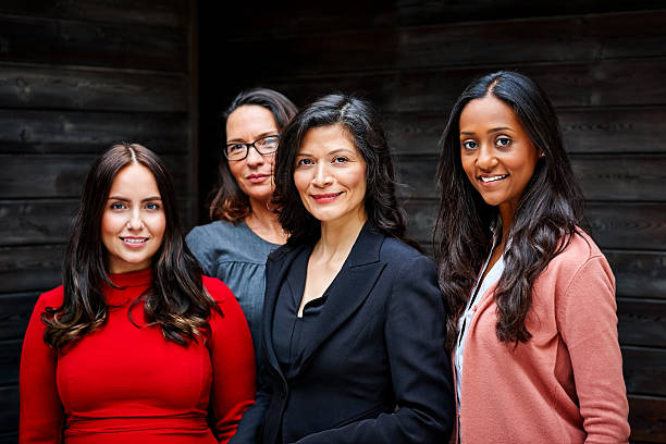 group of businesswomen standing together in office - ejecutiva fotografías e imágenes de stock