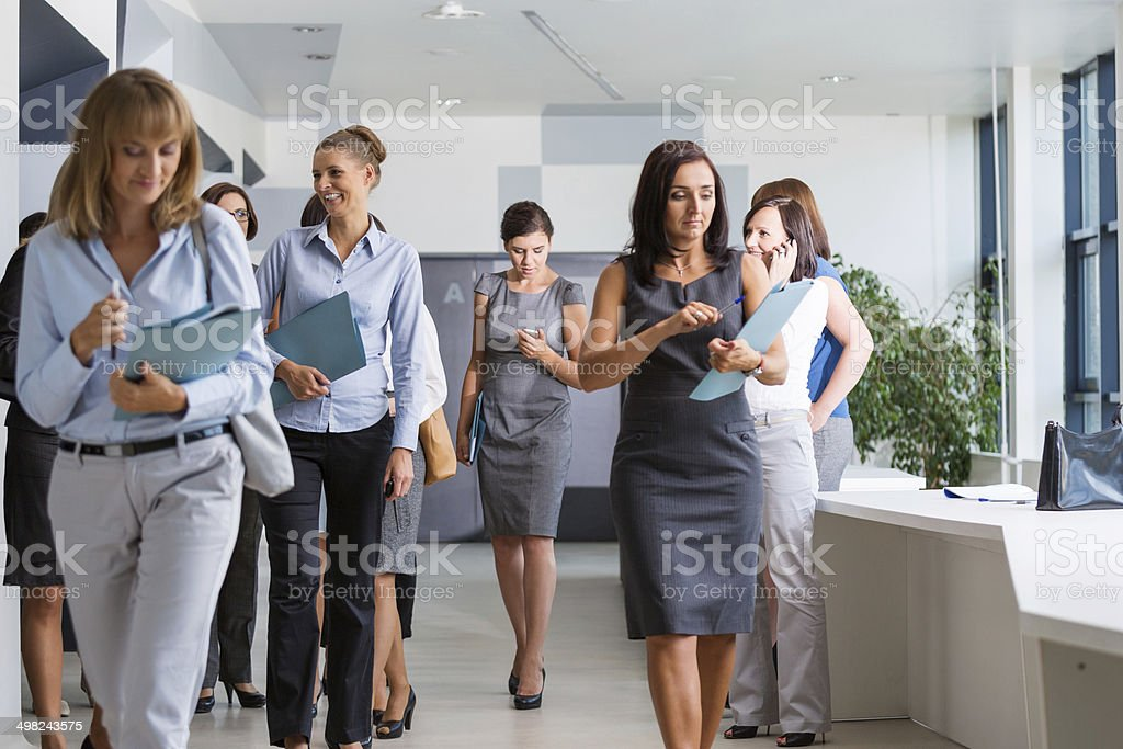 Group of businesswomen walking Group of businesswomen walking down the hall in modern interior. 30-39 Years Stock Photo