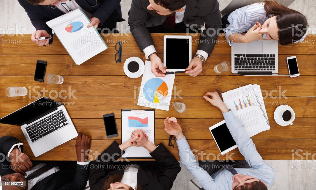 Business meeting top view. Multiethnic people work in office, above...