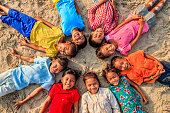 Group of happy Cambodian children are lying in a circle on the beach, Cambodia