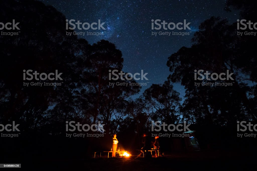 A group of campers stand around a fire with the stars shining brightly above stock photo