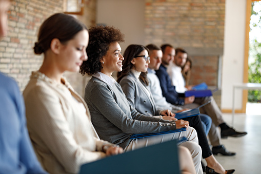 Large group of people sitting in waiting room before job interview for their potential business position. Focus is on happy black woman.