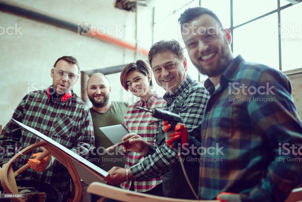 Group Of Carpenters Learning How To Use A Cnc Machine And Posing In