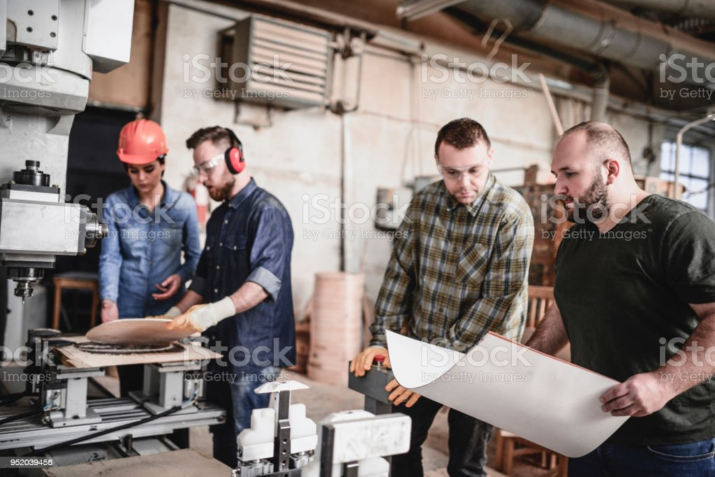 Group of Carpenters Make a Chair in Their Workshop and Get Revised by Senior Supervisor stock photo