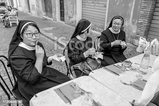 Rome, Italy, May 20 - A group of Catholic nuns grant themselves a moment of relaxation and an ice cream in the alleys of the eternal city, near the Basilica of San Pietro, in the heart of the historic center of Rome.