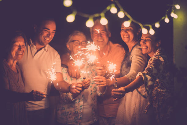 group of caucasian people friends with different ages celebrate together a birthday or new year eve by night outdoor at home. lights and sparkles  with cheerful women and men having fun in friendship - фейерверки и бенгальские огни стоковые фото и изображения