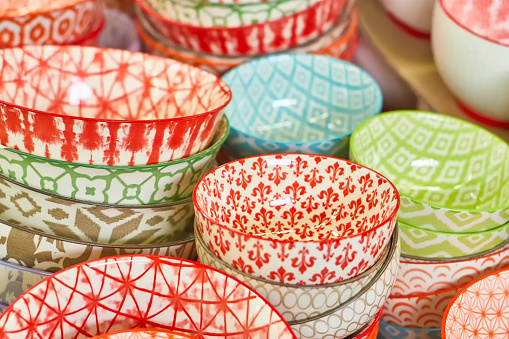 Group of ceramic bowls in the store. Plates with different colorful patterns.