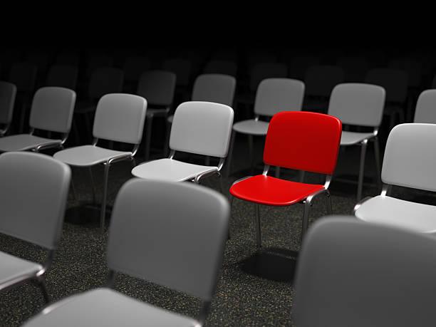 Gruppe von Stühlen mit einem roten Stuhl standing out – Foto
