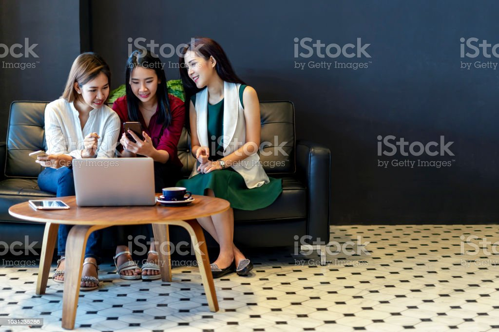 Group of charming beautiful Asian women using smartphone and laptop, chatting on sofa at cafe, modern lifestyle with gadget technology or working woman on casual business concept stock photo