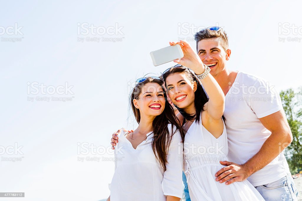 Group of cheerful and beautiful young people taking photos stock photo