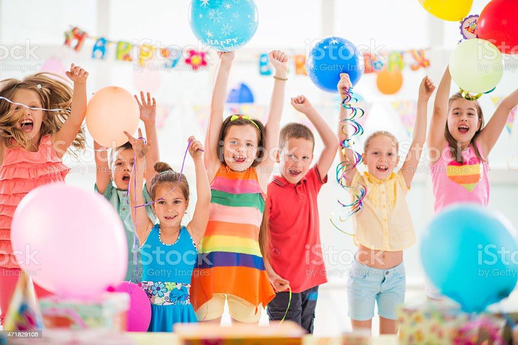 Group of cheerful children enjoying at birthday party. stock photo