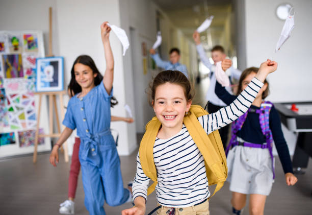 Group of cheerful children going home from school after covid-19 quarantine and lockdown. stock photo