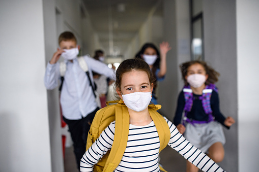 Group of cheerful children going home from school after covid-19 quarantine and lockdown, running.