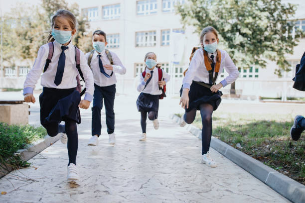 Group of cheerful children going home from school after covid-19 quarantine and lockdown, running. stock photo