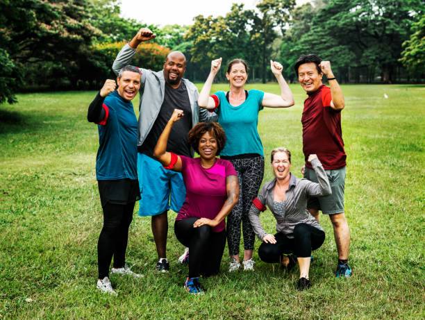 Group of cheerful diverse friends in the park Group of cheerful diverse friends in the park exercising stock pictures, royalty-free photos & images