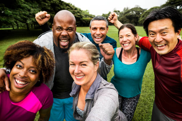 group of cheerful diverse friends in the park - health and beauty stock photos and pictures