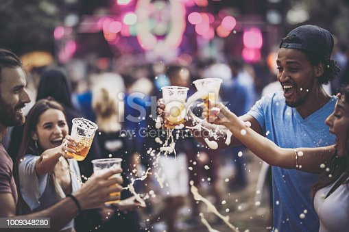 Young happy friends having fun while toasting and spilling beer on a music festival.