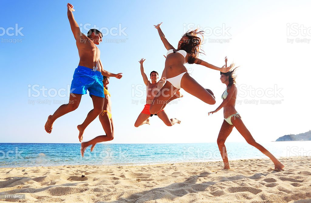 Group of cheerful friends jumping on the beach. royalty-free stock photo