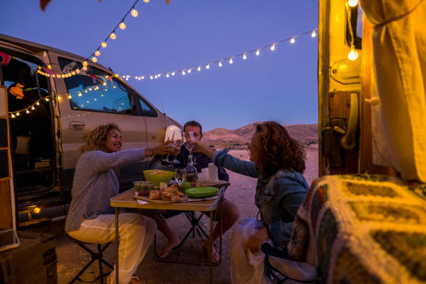 Group of cheerful happy and free people friends celebrate together toasting in outdoor adventure van vehicle travel vacation - enjoy free lifestyle adult man and women in friendship stock photo