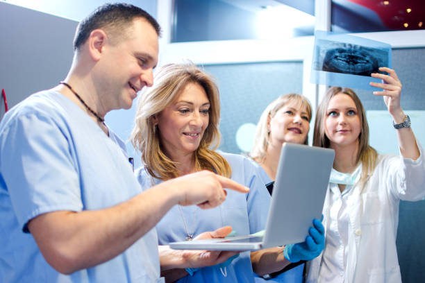 Group of cheerful healthcare workers working together at doctor's office. stock photo