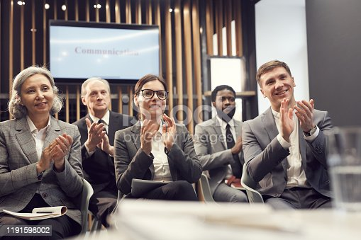 862720340 istock photo Group of cheerful multi-ethnic business conference participants sitting in conference room and applauding speaker after great presentation 1191598002