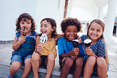 Multi-ethnic best friends children eating ice-cream and having fun on summer holidays