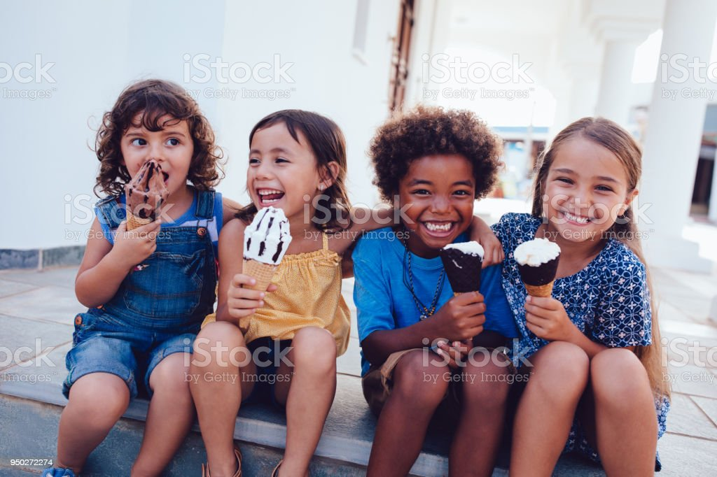 Group of cheerful multi-ethnic children eating ice-cream in summer stock photo