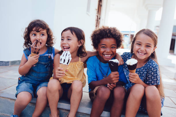 group of cheerful multi-ethnic children eating ice-cream in summer - child stock photos and pictures
