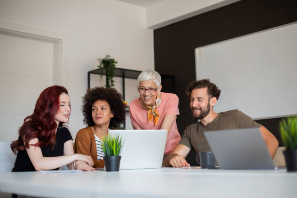 Group of cheerful multi-ethnic colleagues sitting in boardroom and looking at laptop. stock photo