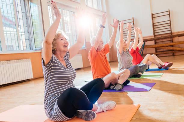 Grupo de la tercera edad alegres haciendo yoga juntos - foto de stock