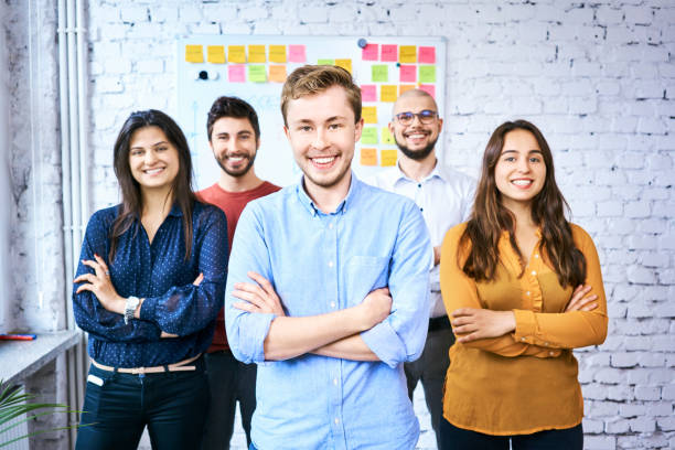 Group of cheerful students looking at camera in classroom. Portrait of young startup entrepreneurs stock photo