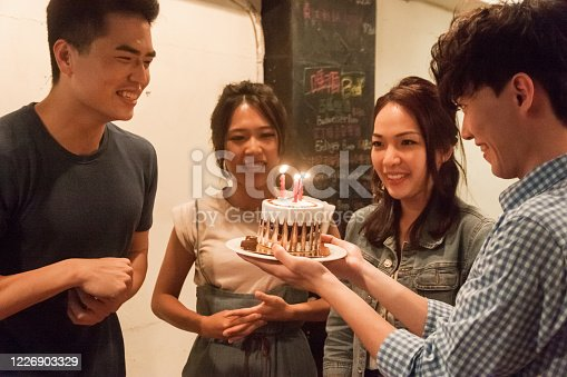Group of cheerful young people singing birthday song to celebrate
