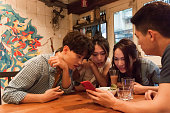 Group of cheerful young people sitting inside having drinks and looking at a smart phone
